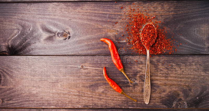Red chili pepper. Full spoon of ground chili pepper and two whole fresh red chilies royalty free stock photos