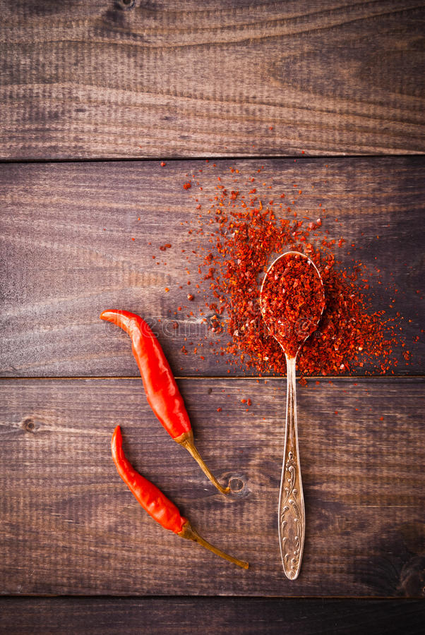 Red chili pepper. Full spoon of ground chili pepper and two whole fresh red chilies on rustic background stock photography