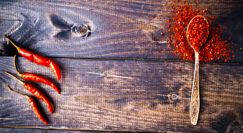Red chili pepper. Full spoon of ground chili pepper and whole fresh red chilies stock photos