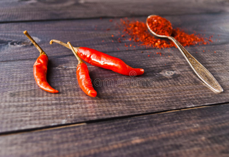 Red chili pepper. Full tea spoon of ground chili pepper and raw red chilies royalty free stock photos