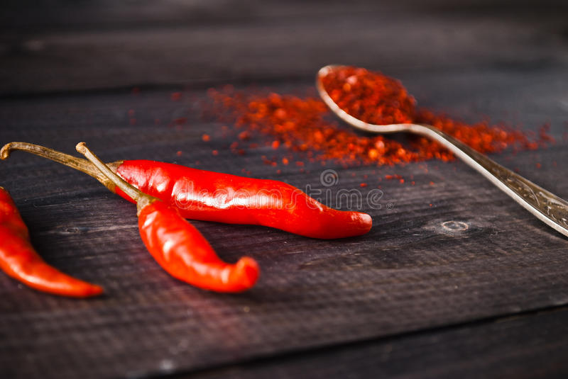 Red chili pepper. Full tea spoon of ground chili pepper and raw red chilies. Close up stock photos