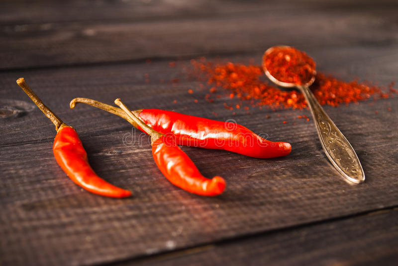 Red chili pepper. Full tea spoon of ground chili pepper and raw red chilies on wooden background stock photography