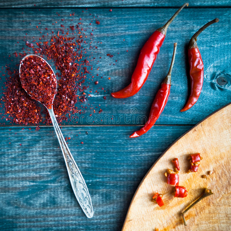 Red chili pepper. Full tea spoon of ground chili pepper, three whole raw red chilies and some slices royalty free stock image