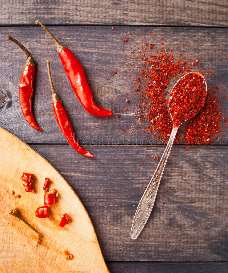 Red chili pepper. Full tea spoon of ground chili pepper, three whole raw red chilies and some slices on cutting board stock images