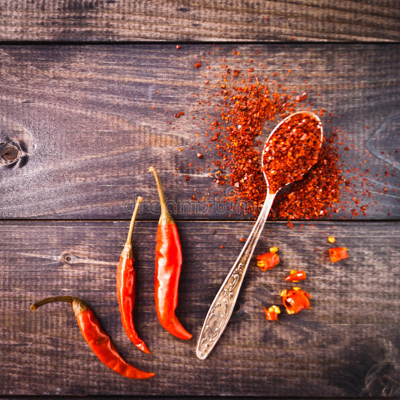 Red chili pepper. Full tea spoon of ground chili pepper, three whole raw red chilies and some slices on rustic wooden background stock image