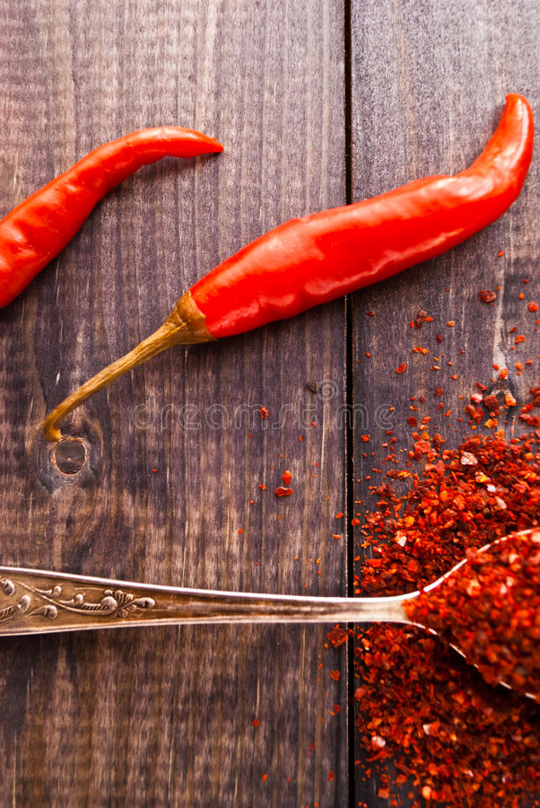 Red chili pepper. Full tea spoon of ground chili pepper and whole raw red chilies. Close up stock image