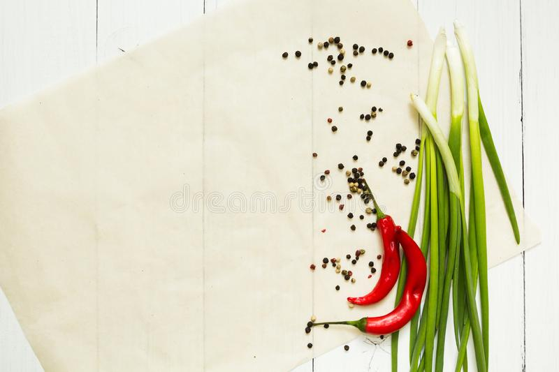 Red chili pepper and green onion with spices on a white wooden background, top view. Space for a dish on a plate or a meal royalty free stock image