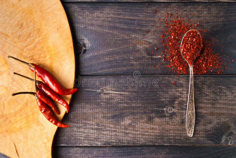 Red chili pepper. Tea spoon of ground chili pepper and whole fresh red chilies on cutting board stock image