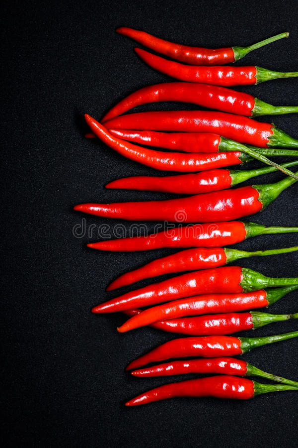 Red chili peppers on black background, Fresh hot chili peppers. Fresh spice ingredient for cooking royalty free stock photos
