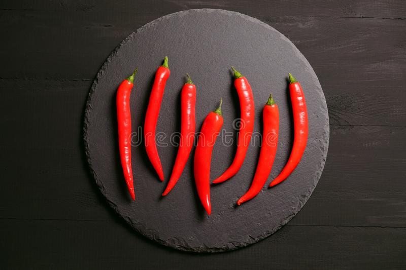 Red chili peppers on black slate plate. View from above, vegetables, food, dish, dark, background, snack, ingredient, sharp, top, wood, wooden, kitchen, cook royalty free stock photos