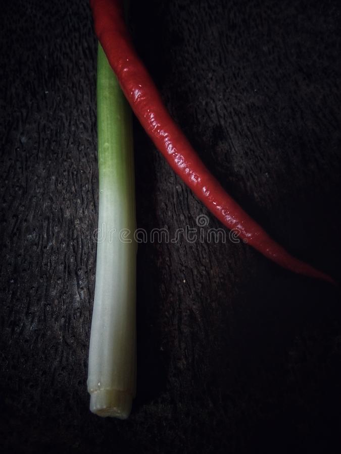 Red chili peppers and green onion. With wooden background stock images