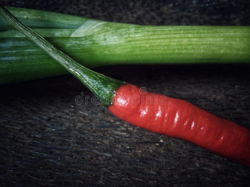 Red chili peppers and green onion. With wooden background royalty free stock photos