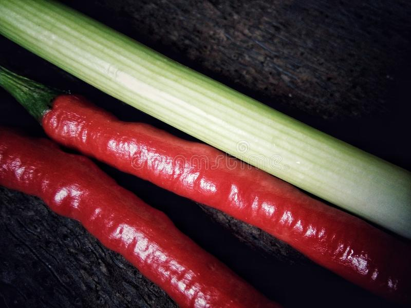 Red chili peppers and green onion. With wooden background stock photography