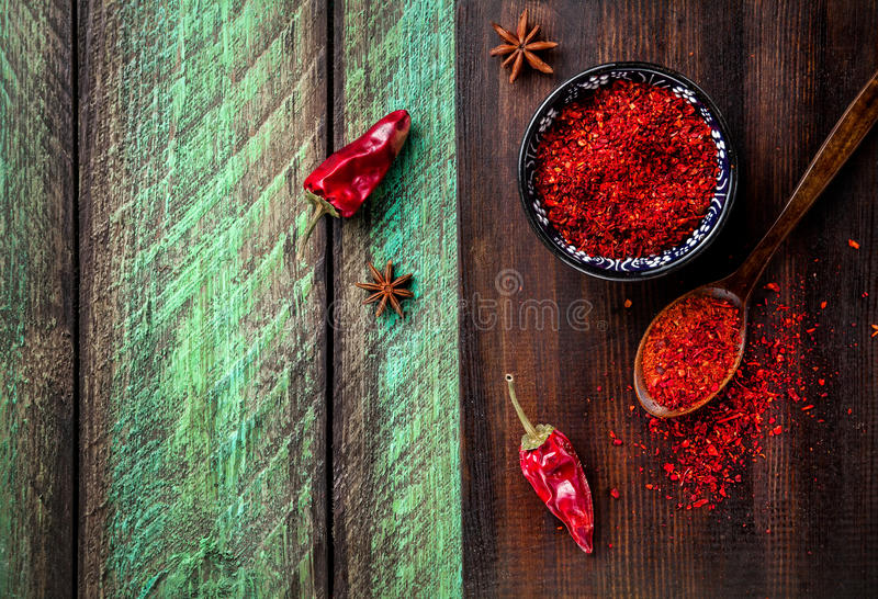 Red Chili on wooden background. Red Chil pepperi and paprika powder on dark cutting board at green wooden table stock photo