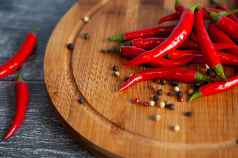 Red chilly peppers on a round wooden board stock photo