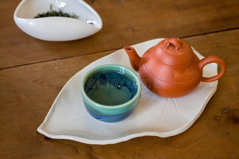 Red Chinese Clay pot and small blue and green tea cup on exquisite leaf shaped white plate. Red Chinese Clay pot and small blue and green ceramic tea cup on stock photos