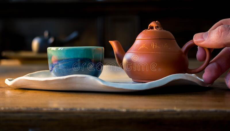 Red Chinese Clay pot and small blue and green tea cup on exquisite leaf shaped white plate with hand. Red Chinese Clay pot and small blue and green ceramic tea royalty free stock photo