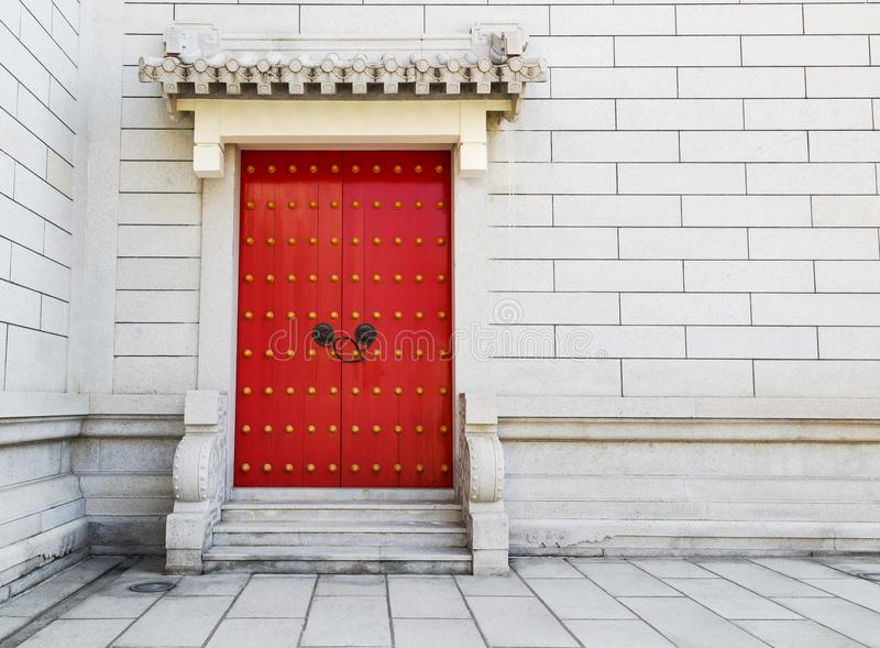 Red Chinese door with locked key and bronze lion head knob on co. Red Chinese door with locked key and bronze lion head knob on white concrete wall stock image