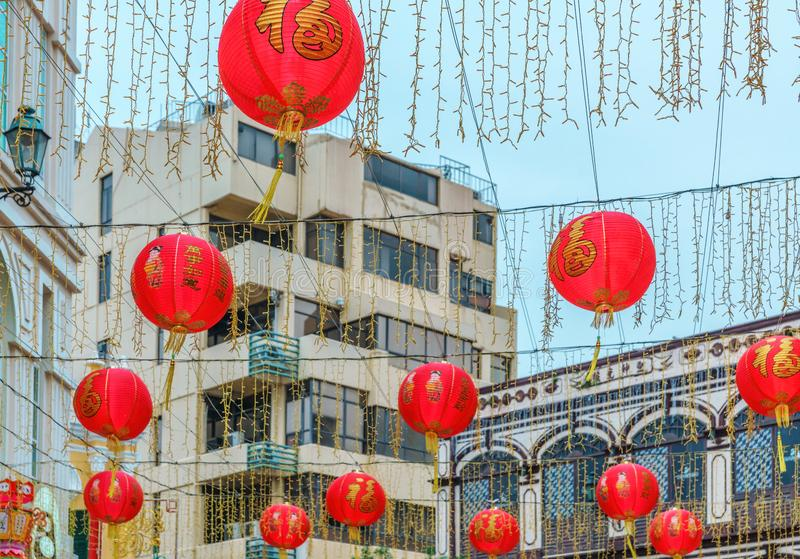 Red Chinese lantern garlands used as decorations before Chinese New year celebration hang outdoors on building background stock image