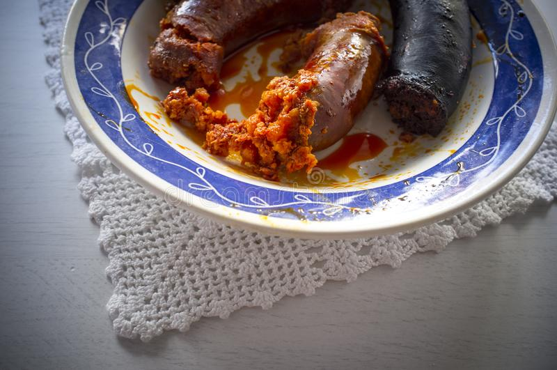 Red chorizo and black sausage morcilla just boiled on a plate over knitting cloth. Closeup royalty free stock photos