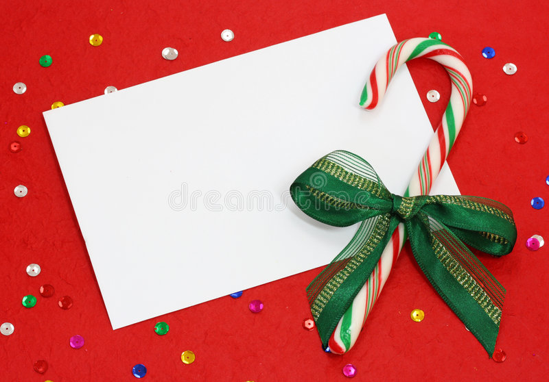 Red christmas background. With blank note and candy cane on red stock image