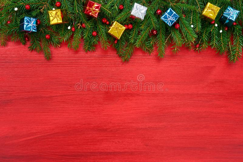 Red Christmas background. Christmas fir tree with decorative gifts on red wooden background royalty free stock images