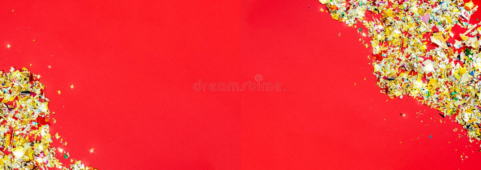 Red Christmas background , holiday concept. Place for text. Red background on which a lot of multi-colored clapperboard foil and stars confetti, holiday concept stock images