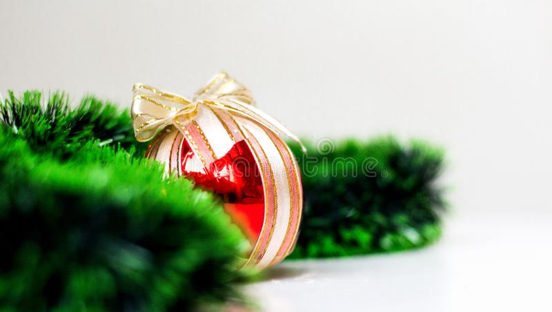 Red christmas ball with bow and spruce green garland on light background. Close-up, copyspace, banner stock photos