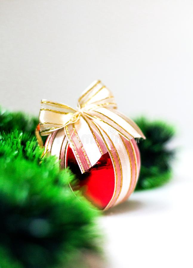 Red christmas ball with bow and spruce green garland on light background. Close-up, copyspace royalty free stock photos
