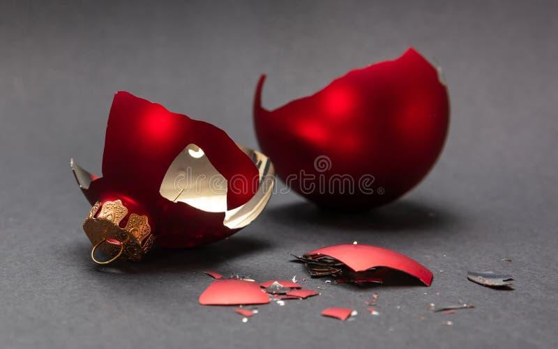 Red Christmas ball broken, dark gray background, closeup view stock photography