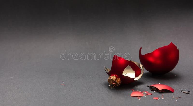 Red Christmas ball broken, dark gray background, closeup view royalty free stock image