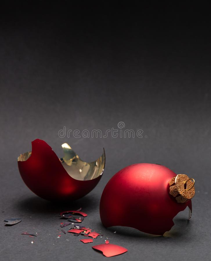 Red Christmas ball broken, dark gray background, closeup view royalty free stock photography