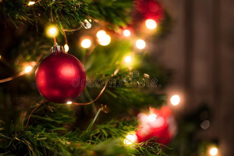 Red Christmas ball on a Christmas tree. With a garland on the background of a wooden wall stock image