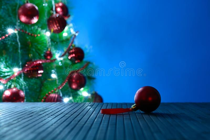 Red Christmas ball on surface opposite the decorated fir royalty free stock images