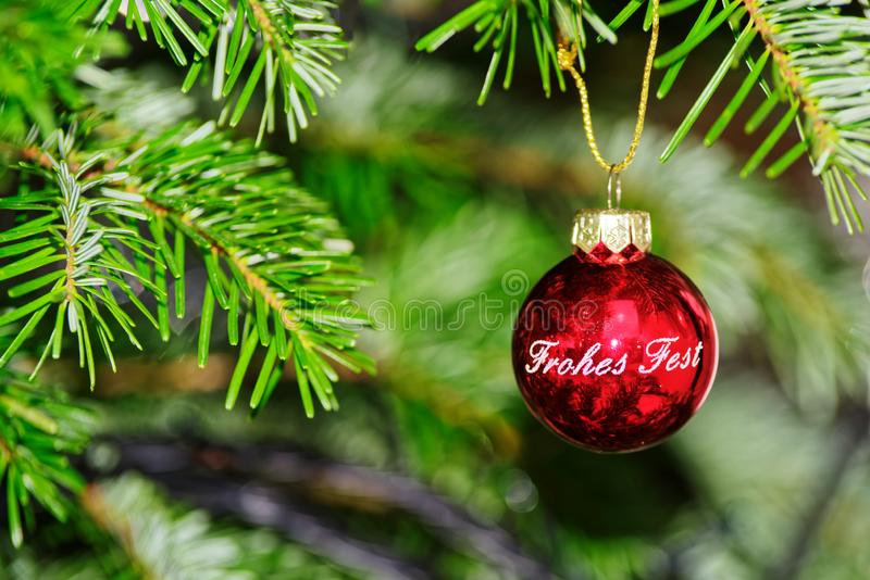 Red christmas ball with a text Happy Holiday in German hanging on fir branch royalty free stock image