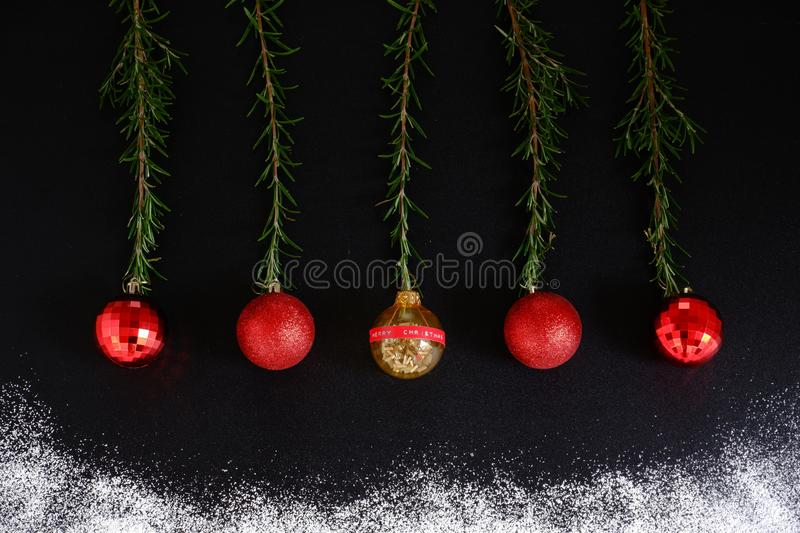 Red christmas balls on black background with snow. Hanging red christmas balls on black background with snow and herb rosemary royalty free stock photos