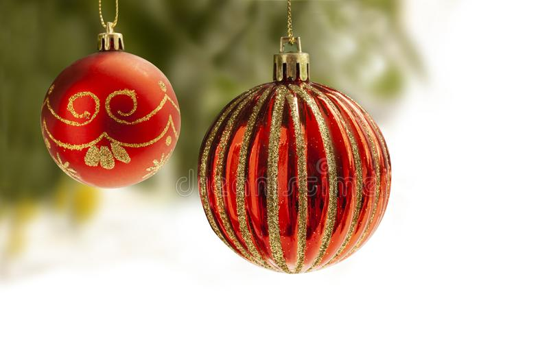 Red Christmas balls with gold decoration hanging from a Christmas tree with blurry background. Ball are partly isolated on white f stock photo