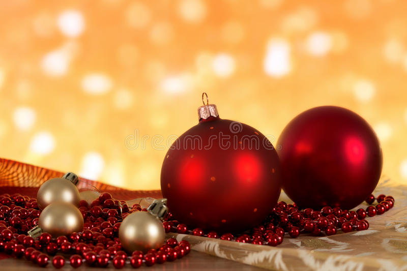 Red Christmas balls and golden beads on a blurred background. royalty free stock photography