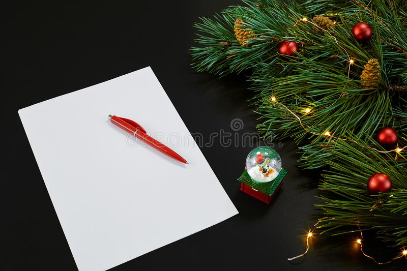 Red Christmas balls and notebook lying near green spruce branch on black background top view. Space for text stock image
