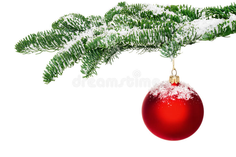 red christmas bauble hanging from a snow-covered twig stock photo