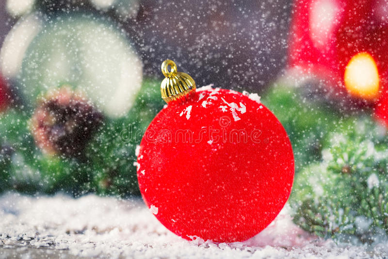 Red Christmas bauble with snow on wood royalty free stock images