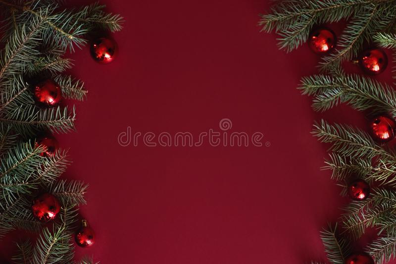 Red Christmas baubles decoration on red background with copy space. New Year greeting card. Minimal style. Flat lay.  royalty free stock photo
