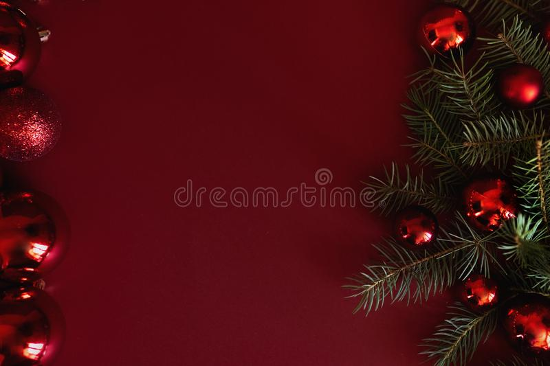 Red Christmas baubles decoration on red background with copy space. New Year greeting card. Minimal style. Flat lay. / stock photos