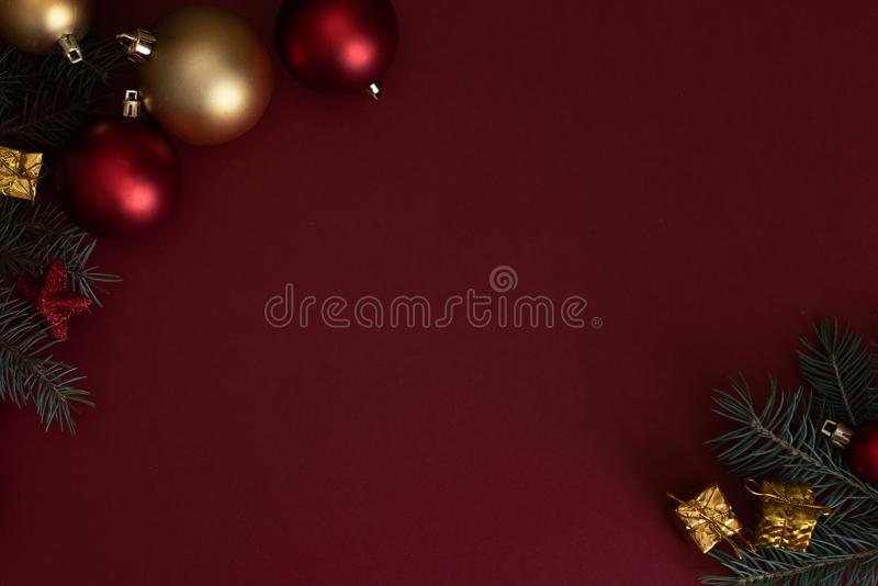 Red Christmas baubles decoration on red background with copy space. New Year greeting card. Minimal style. Flat lay. / royalty free stock image