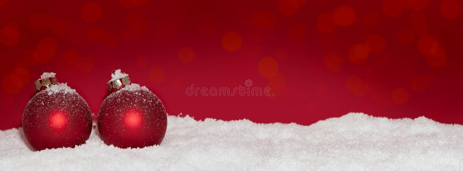 Red Christmas baubles in the snow royalty free stock photos