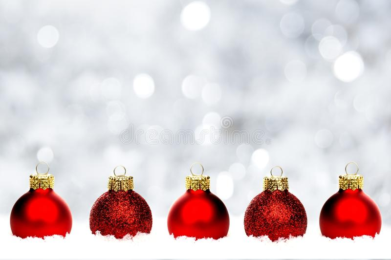 Red Christmas baubles in snow with silver background stock photos