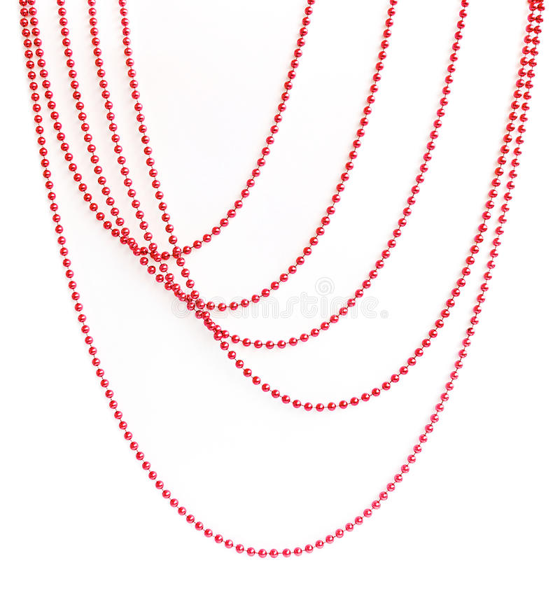 Red Christmas bead garland hanging on white. Background stock image