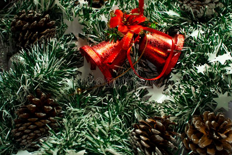 Red Christmas bells on green tinsel, and cones around. Christmas decor items stock photos