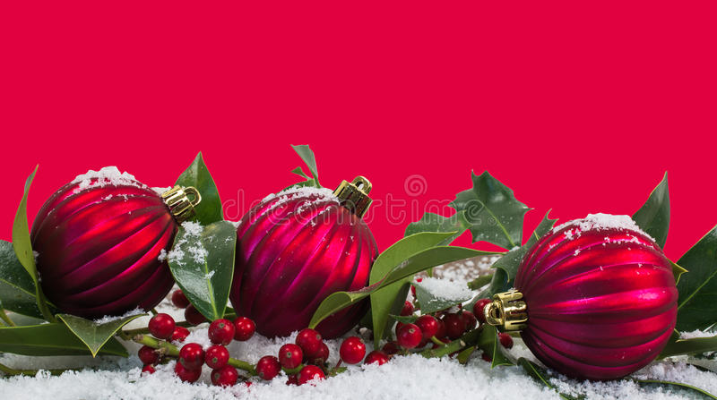 Red Christmas border background with baubles in the snow. Red background with border of Christmas baubles, red berries and holly leaves in the snow.nChristmas stock images