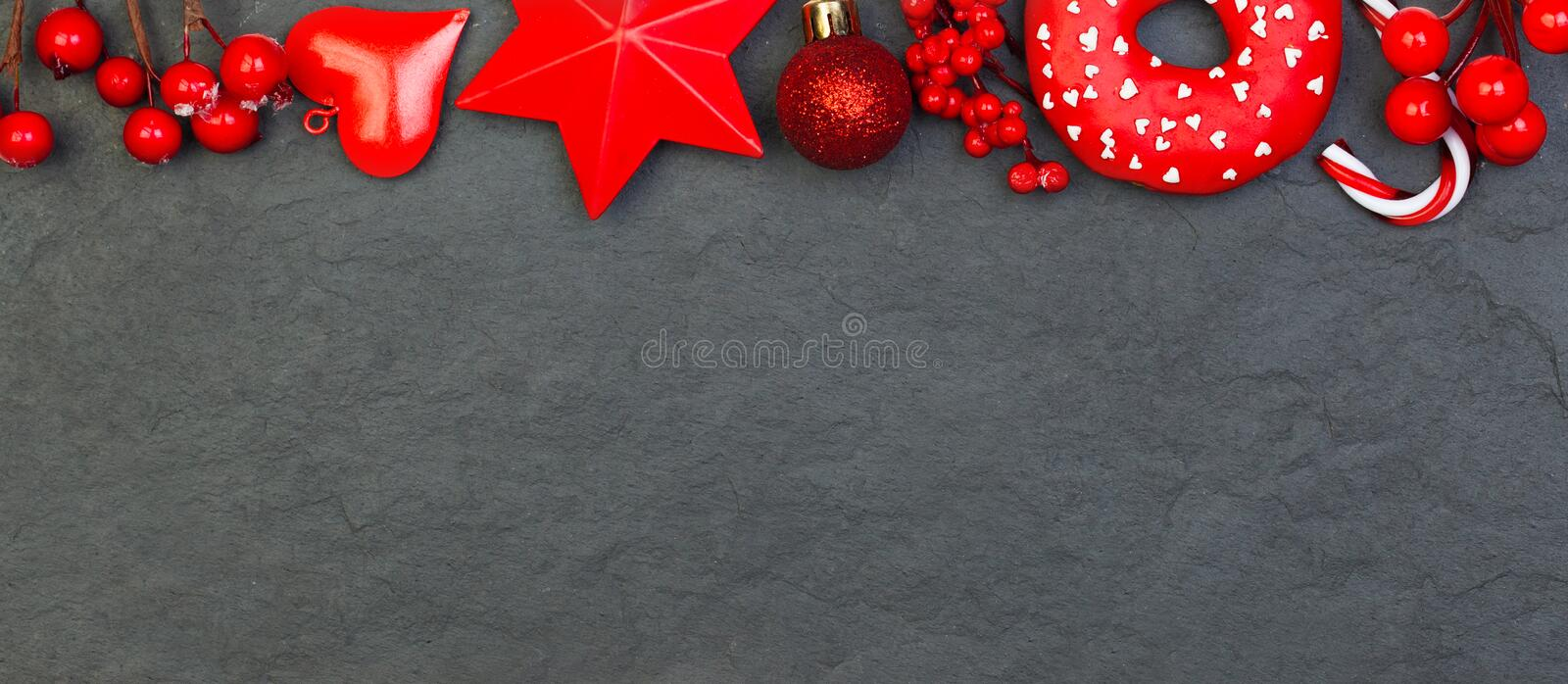 Red Christmas border on black background. Xmas composition with holly berries, red decor and glass baubles.  stock photography